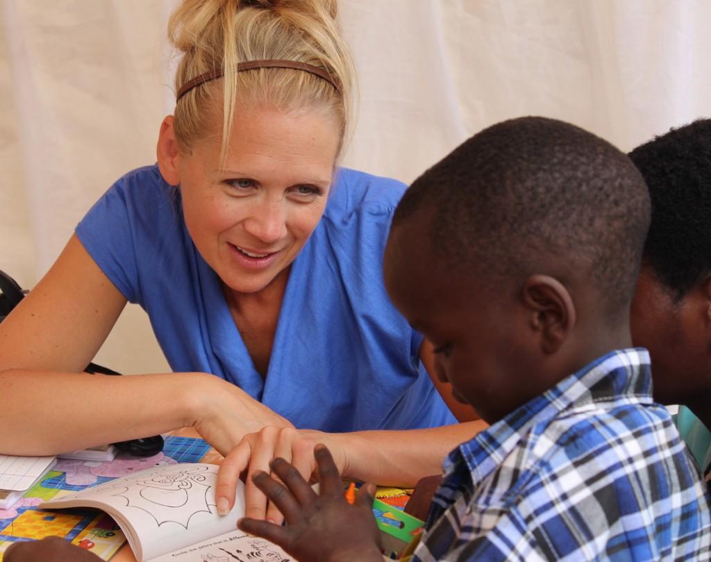 Anoka-Ramsey Spanish instructor Shannon Kirkeide talks to a villager on a trip to Rwanda during summer 2013. COURTESY KELLI MCDONALD