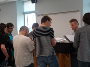 The men of the choir working hard with Dr. B on a tricky part in their song.