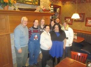 Group giving a baby shower for Delia Pinto. Back row (Left to right): Bob Walz, Rochelle Peace, Courtney Bushway, Megan Harris and Stephen Pearce (all students at ARCC). Front row (left to right): Delia Pinto, Heather Keevers of Options for Women LifeCare Center and Betty Mitchell of Options for Women LifeCare Center, taken at Perkins Restaurant, North Branch. Missing in photo: Karl Zabinski, Cierra Amerud, Calli Johnson, Kimberly Holmes, Andrea Miller and Sarah Strubel (ARCC students) and other Honduran immigrants in the Intercambio: Javier Riveria, Tulio Portello and Elena Erazo Melara