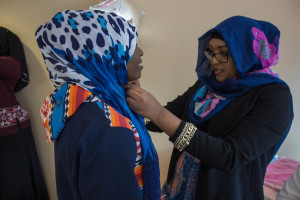 PHOTO BY MIRANDA SCHMIDT A student from the Muslim Student Association, Najma Ali, dresses a participant, Anastasia Mukanyandwi, in a hijab for Islamic Awareness week in April 2015
